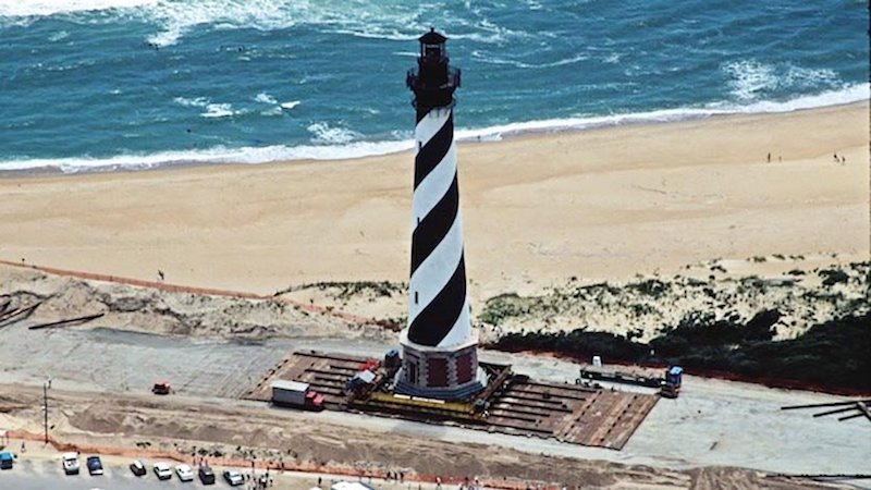 Above: An excellent example of a well-managed strategic retreat from the coast occurred in 1999, when the Cape Hatteras Lighthouse on North Carolina's Outer Banks was moved 2,900 feet back from an eroding shoreline, a move that cost $12 million. When completed in 1870, the Cape Hatteras lighthouse had been located a safe 1,500 feet inland from the ocean, but natural barrier island erosion processes, augmented by rising seas and storm-driven tides, had reduced this distance to just 120 feet by 1999. Locals were strongly opposed to the move, believing it would harm the tourist industry. Ironically, the lighthouse is now more of a tourist attraction than ever. On the Outer Banks of North Carolina, the regional slope of the land is 1 to 10,000, which means in theory that a 1-foot rise in sea level could move the shoreline about 2 miles. Thus, the lighthouse will likely have to be moved again later this century. Image credit: National Park Service.